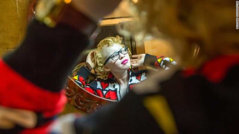 A contestant poses for the camera while getting ready for the pageant. image via CNN